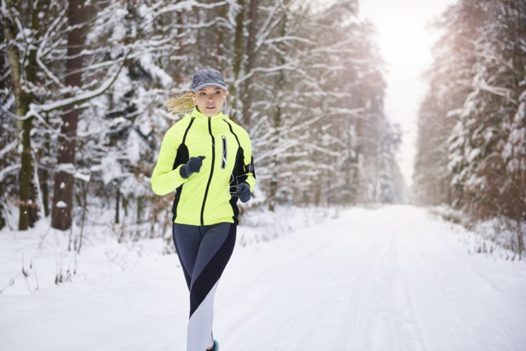 Front view of woman running in winter forest